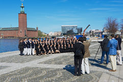 Asian tourists make group photo with the City Hall (Stadshuset) at the background in Stockholm, Sweden. STOCKHOLM, SWEDEN - APRIL 28, 2011: Unidentified asian Royalty Free Stock Photos