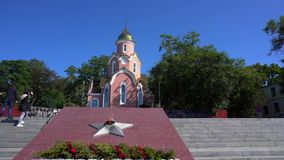 Asian tourists strolling by the eternal flame opposite the Church of the Holy Apostle Andrew the First Called in Vladivostok in th. E summer of 2018 stock video footage