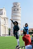 Asian tourists take pictures  of the Leaning Tower of Pisa Royalty Free Stock Photography