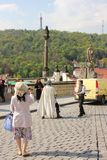 Asian tourists taking photo near Prague Castle playing battle with medieval knight reenactment scene stock photography