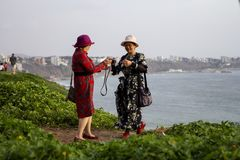 Asian tourists taking photos of the sunset at Malecón de la Costa Verde royalty free stock photography