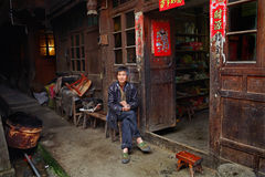 Asian trader in green sneakers, sits near a village shop. Stock Photos
