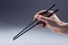 Asian tradition. Asian eating with two Handle Chopsticks Royalty Free Stock Photo