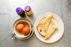 Asian traditional breakfast of half boiled eggs with toast bread. Asian traditional breakfast combination of half boiled eggs and toast bread with butter and Royalty Free Stock Images