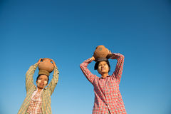 Asian traditional farmers carrying pot on head Stock Photos