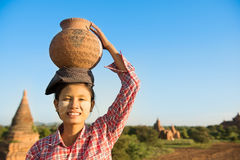 Asian traditional female farmer carrying clay pot on head Royalty Free Stock Photos