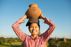 Asian traditional female farmer carrying clay pot Royalty Free Stock Photo
