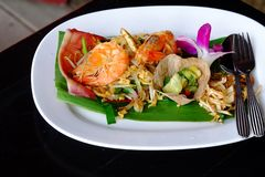 Fried noodle of Padthai with shrimps on top, a Thai famous food in a white plate on black dinning table stock image