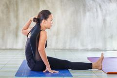 Asian trainee strong woman practicing difficult yoga pose in a concrete background Stock Image
