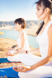 Asian trainer conducts classes of group yoga outdoor. At mountain. Concept of a healthy lifestyle and the right attitude to life. China Royalty Free Stock Photo