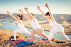 Asian trainer conducts classes of group yoga outdoor. At mountain. Concept of a healthy lifestyle and the right attitude to life. China Royalty Free Stock Photos