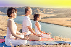 Asian trainer conducts classes of group yoga outdoor. At mountain. Concept of a healthy lifestyle and the right attitude to life. China Stock Image