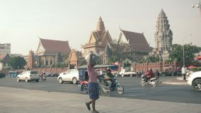 Asian transport traffic and pedestrians on the central waterfront street with Wat Ounalom on b stock video footage