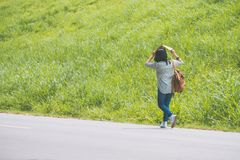 Asian traveler with backpack walking on country road and use map. For protect sunshine and looking forward to see direction near green grass in sunny day,Alone Royalty Free Stock Image