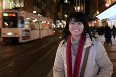Asian Traveler in Europe. Asian woman traveler walking along the sidewalk of Geneva's shopping district in Switzerland at night Stock Photo