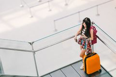 Asian traveler girl, college student using smartphone call or chat at airport with luggage, backpack. Web check in, lonely travel. Cute teenage Asian traveler Royalty Free Stock Photos