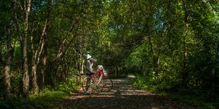 Asian traveler holiday relax with bicycle in nature park. Asian traveler holiday relax drinking water with bicycle in Bang Krachao nature park Royalty Free Stock Images