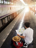Asian traveler man with belongings waiting for travel by train Stock Photos