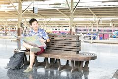Asian traveler siting and holding map at platform stock images