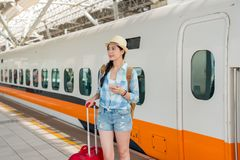 Asian traveler woman arrive the destination. By high speed rail standing on the platform of the station with holding a smartphone. holiday travel vactation royalty free stock photos