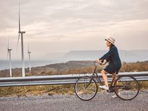 Asian traveler woman in jean dress  with classic bicycle road in retro contemporary style royalty free stock photography