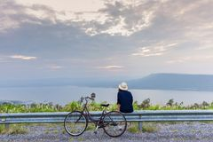 Asian traveler woman in jean dress relaxing holiday. With classic bicycle on nature road with lake mountain wind turbine background royalty free stock images