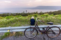 Asian traveler woman in jean dress relaxing holiday. With classic bicycle on nature road with lake mountain wind turbine background stock images