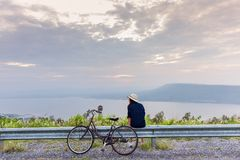 Asian traveler woman in jean dress relaxing holiday. With classic bicycle on nature road with lake mountain wind turbine background stock photography