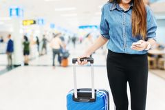 Asian Traveler women looking for flight in smartphone at airport terminal Travel concept stock image
