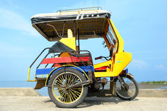 Asian tricycle. Asian colourful tricycle parked in front of a tropical bay Stock Photo