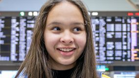 Asian tween girl in front of airport arrivals board stock photography