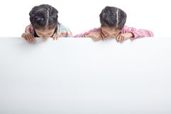 Asian twin sisters  behind empty billboard look at the billboard Royalty Free Stock Image