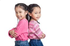 Asian twin sisters fold arms  standing back to back Stock Photo