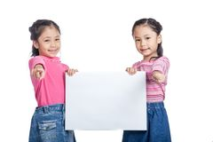 Asian twin sisters  hold a blank sign  point to camera Royalty Free Stock Image