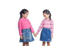 Asian twin sisters holding hands look at the hand Stock Image