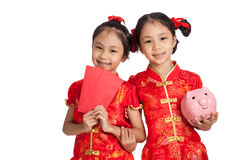 Asian twins girls in  chinese cheongsam dress with coin bank and Royalty Free Stock Images