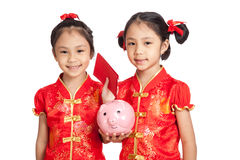 Asian twins girls in  chinese cheongsam dress with coin bank and Stock Images