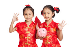 Asian twins girls in  chinese cheongsam dress with coin bank and Stock Photography