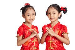 Asian twins girls in  chinese cheongsam dress with gesture of co Royalty Free Stock Photo