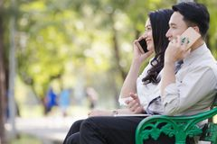 Asian two business men and woman. Asian two business men and women work relaxation in park with smartphone Stock Images