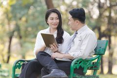 Asian two business men and woman. Asian two business men and women work relaxation in park with smartphone Stock Photo