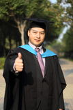 Asian university graduate. With thumb up Royalty Free Stock Images