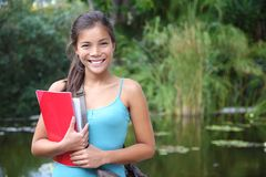 Asian university student. Student. Asian university student holding her books outdoors in the campus park. Cute young mixed race chinese / caucasian woman Royalty Free Stock Photography