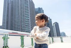 Asian urban kid lifestyle on urban city. Asian kid smart portrait posting on high building and skytrain in capital city. Street portrait kid with urban lifestyle royalty free stock images
