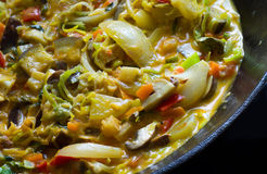 Asian vegetable curry in a black wok pan of iron Royalty Free Stock Photo
