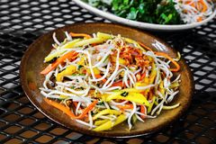 Asian vegetable salad on metal table. Asian vegetable salad on plate, part of plate with main dish on metal table stock photos