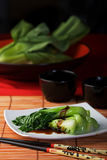 Asian vegetables with oyster sauce. Dish of steamed bok choy with oyster sauce on white plate amid Asian style table setting Royalty Free Stock Photo