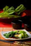 Asian vegetables with oyster sauce. Dish of steamed bok choy with oyster sauce on white plate amid Asian style table setting Stock Image