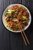 Asian vegetarian food udon noodles with baby bok choy, shiitake mushrooms, sesame and pepper close-up on a plate. Vertical top. Asian vegetarian food udon stock photos