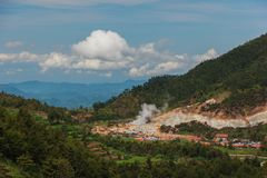 Asian village in jungle mountains and cumulus clouds stock image